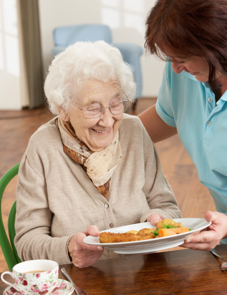 care worker helping elderly in care home
